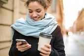 Young woman walking in the city with a smartphone and a latte in her hand.
