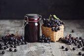 Aronia jam next to fresh berries. Homemade aronia jam in glass jar with fresh aronia berries on wood poster