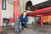 Smiling Mechanic Examining Car Tire While Crouching In Workshop poster