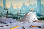 Architectural Drawing Plan With Blueprint Rolls, Safety Helmet And Drawing Tools On Working Table. B poster