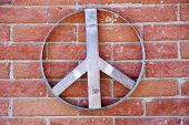 Peace Sign. A wooden peace sign on a brick wall outdoors.  poster