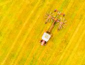 Aerial view to harvester on meadows. Harvest of hay field. Industrial background on agricultural the poster