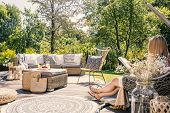 Woman Reading Book While Relaxing At Terrace With Rattan Furniture In The Garden. Real Photo poster