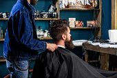Man With Beard And Mustache Sits In Barbershop, Beauty Supplies On Background. Barbershop Concept. M poster