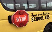 An empty school bus with red stop warning sign parked aside. Text Scool bus written in English a poster