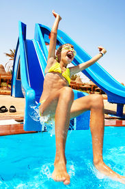 pic of amusement park rides  - Child on water slide at aquapark - JPG