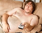 stock photo of obese man  - Fat man is laying on the couch topless watching the TV - JPG
