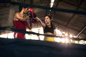 stock photo of pugilistic  - Young woman exercising with trainer at boxe and self defense lesson - JPG