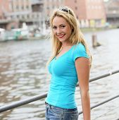 picture of curvaceous  - Beautiful curvaceous young blonde woman with a lovely figure and bright smile standing alongside an urban river - JPG