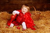 stock photo of riding-crop  - Little girl is sitting on pile of straw with apple - JPG