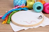 The embroidery hoop with canvas and bright sewing threads for embroidery in the table