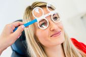 Optometry concept - pretty young woman having her eyes examined by an eye doctor (color toned image;