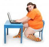 Overweight girl in a school desk with laptop.