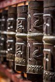 Tibetan Buddhist prayer wheels in Buddhism temple. Shallow depth of field. Rewalsar, HImachal Prades