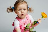 stock photo of pink rose  - Cute toddler with orange rose in hand on grey background - JPG