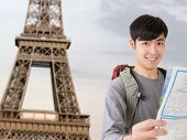 Asian young traveler of man hold map and look at you in front of the famous landmark, Eiffel Tower, France. poster