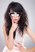 stock photo of raised-eyebrow  - sexy young fashion woman posing with a hand on her waist and with a finger on her face while looking at the camera with an eyebrow raised behind her sunglasses - JPG