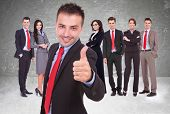 image of leader  - young business man leader of a successful team making the thumbs up ok gesture - JPG