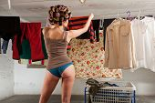 girl housewife stretches clothes in the basement