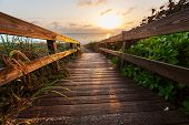 stock photo of sunrise  - boardwalk on beach - JPG