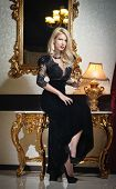 foto of lace-curtain  - Young beautiful luxurious woman in long elegant black dress - JPG
