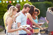 stock photo of buffet  - Group Of Friends Having Outdoor Barbeque At Home - JPG