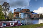 stock photo of william shakespeare  - Narrowboat moored on the River Avon by the Royal Shakespeare Company theatre - JPG