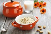 stock photo of porridge  - Porridge with almonds in an orange bowl on the table