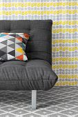 stock photo of futon  - Sofa with colorful cushion on bright floral background - JPG