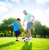 picture of pre-adolescent child  - Little boy playing soccer with his father - JPG
