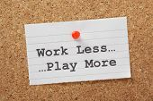 pic of stress relief  - The phrase Work Less Play More typed on a paper note and pinned to a cork notice board as a reminder - JPG