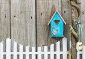 image of locust  - Teal blue and pink birdhouse hanging over white picket fence next to vine wrapped honey locust tree with wooden hearts - JPG