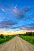 picture of dirt road  - dirt road to sunset through the fields