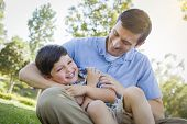 stock photo of tickling  - Loving Young Father Tickling Son in the Park - JPG