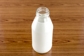 image of milkman  - milk in a glass of bottle on wood table background - JPG