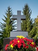 foto of tribute  - Black granite tombstone cross and red and yellow floral tribute - JPG