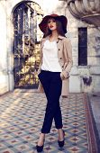 stock photo of palace  - fashion outdoor photo of beautiful elegant woman with dark straight hair wearing elegant coat and hatposing in palace - JPG