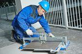 picture of overhauling  - industrial tiler builder worker working with floor tile cutting equipment at repair renovation work - JPG