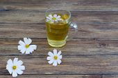 foto of chamomile  - chamomile and chamomile tea on a wooden table