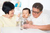 foto of grandparent child  - Asian family saving money indoor - JPG
