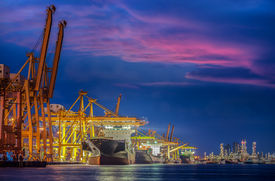 picture of shipyard  - Container Cargo freight ship with working crane bridge in shipyard at dusk for Logistic Import Export background - JPG
