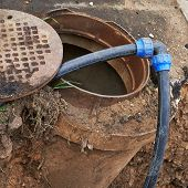 foto of manhole  - Cleaning equipment tubes in a sewer manhole composition - JPG