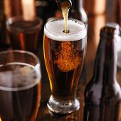 foto of bottles  - pouring beer from bottle into glass at bar - JPG
