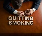 pic of quit  - Phrase Quitting Smoking made of wooden block letters and devastated middle aged caucasian man in a black suit sitting at the table with the glass of whiskey - JPG