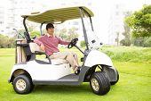 stock photo of buggy  - Golfer driving his golf buggy looking at camera at the golf course - JPG