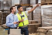 foto of warehouse  - Warehouse worker showing something to his manager in a large warehouse - JPG