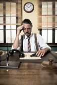 picture of 1950s  - Depressed businessman sitting at desk and holding a gun 1950s style office - JPG