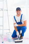 picture of handyman  - Full length portrait of smiling handyman using paint roller in tray at home - JPG
