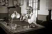 picture of 1950s  - Cheerful director sitting at office desk 1950s vintage office.