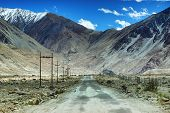 pic of jammu kashmir  - A concrete road towards beautiful rocky mountains and snow peaks of Himalaya Leh Ladakh Jammu and Kashmir India - JPG